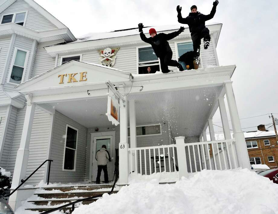 From left, Worcester Polytechnic Institute freshmen Kyle Foster and Steven Como, both members of the Tau Kappa Epsilon fraternity, jump from the fraternity house porch roof into a steep snow bank on Wachusett Street in Worcester, Mass., in the aftermath of an overnight storm on Saturday, Feb. 9, 2013. Photo: Paul Kapteyn, Associated Press / Worcester Telegram & Gazette