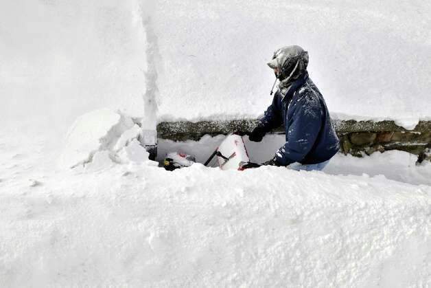 Andrew Stratis pushes his snow thrower through deep snow as he tries to clear the sidewalk in front of his house on Holden Street in Worcester, Mass., in the aftermath of an overnight storm on Saturday, Feb. 9, 2013. Photo: Paul Kapteyn, Associated Press / Worcester Telegram & Gazette