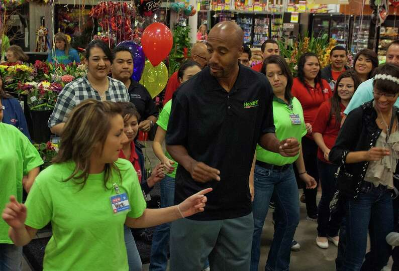 Retired San Antonio Spur Bruce Bowen (middle) joins HEB officers, employees and customers as they br