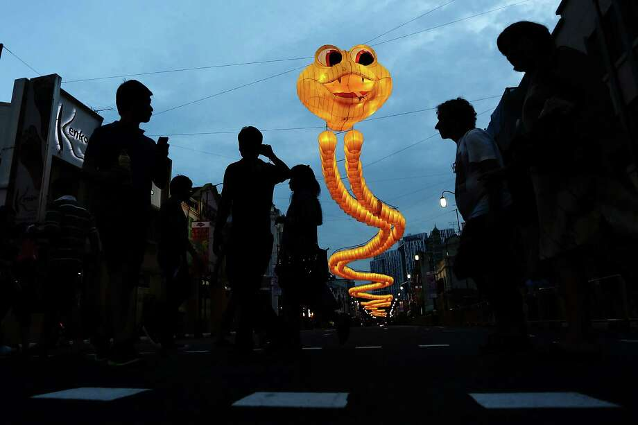 A snake shaped sculpture made from about 850 yellow sky lanterns looms over a road in Chinatown on February 9, 2013 in Singapore. Thousands gathered today to celebrate the Chinese New Year and welcome the the Year of the Snake, with new year's day falling on February 10. Chinese new Year is the most important festival in the Chinese calendar and is celebrated in Singapore and many other Southeast Asian countries with significant Chinese Populations. Photo: Suhaimi Abdullah, Getty Images / 2013 Getty Images