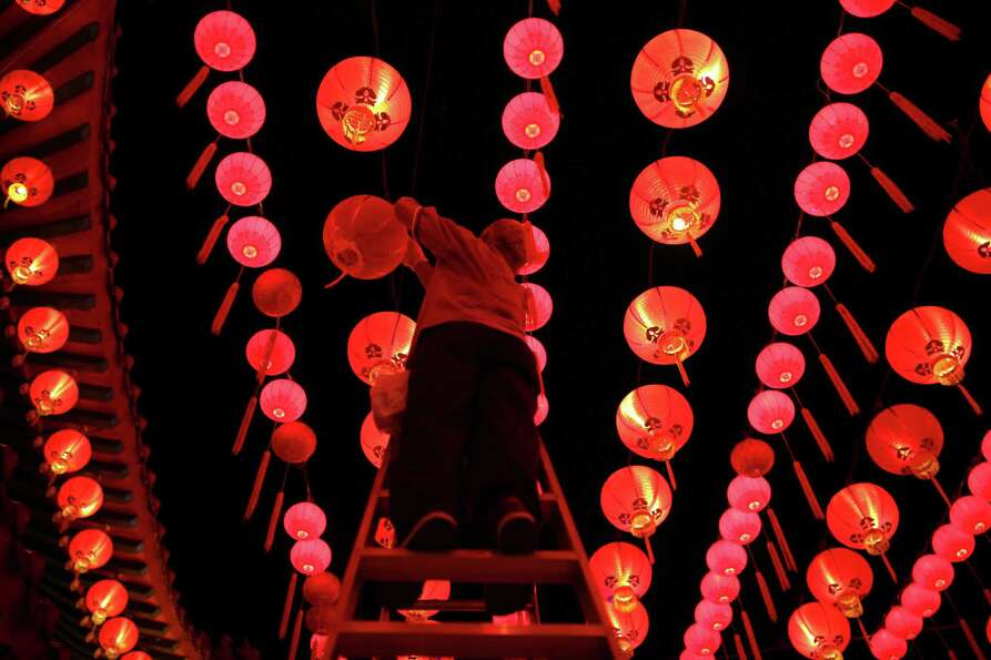 A worker changes the lights bulbs in lanterns ahead of Chinese New Year celebrations at the Thean Ho