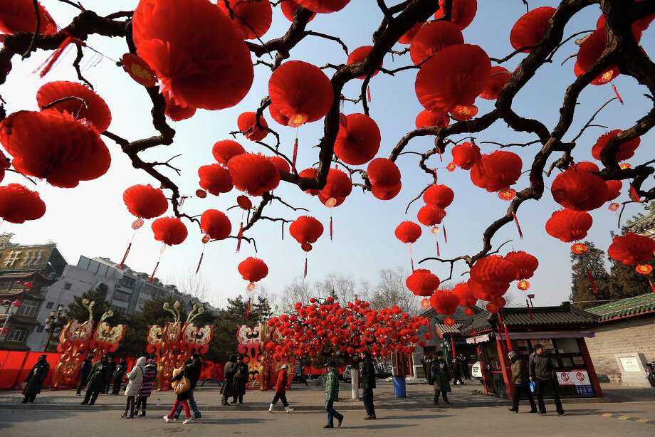 Visitors stroll near the trees decorated with red lanterns ahead of Chinese New Year celebrations during the opening ceremony of the Spring Festival Temple Fair at the Temple of Earth park on February 9, 2013 in Beijing, China. The Chinese Lunar New Year of Snake also known as the Spring Festival, which is based on the Lunisolar Chinese calendar, is celebrated from the first day of the first month of the lunar year and ends with Lantern Festival on the Fifteenth day. Photo: Feng Li, Getty Images / 2013 Getty Images