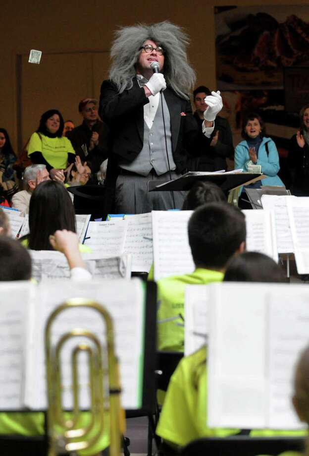 Master of ceremonies Brian Austin, center, auctions off the opportunity for an audience member to conduct a song during the Empire State Youth Orchestra's annual Playathon on Saturday, Feb. 9, 2013, at Crossgates Mall in Guilderland, N.Y. Some listeners were dropping dollar bills from the upper level. The event raises awareness and funds for the ESYO. (Cindy Schultz / Times Union) Photo: Cindy Schultz / 10021084A