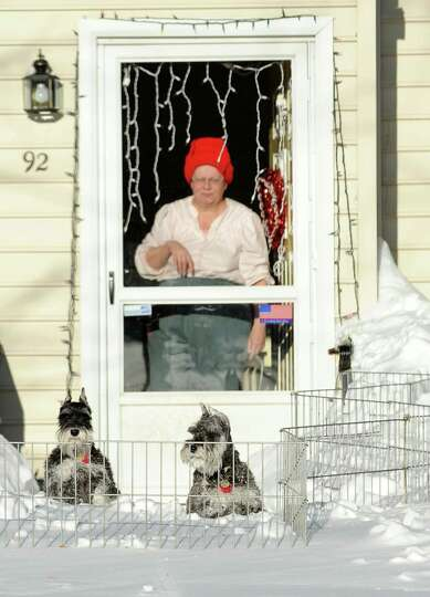 A woman looks out her front door at her two small dogs penned in her yard on Pansy Rd in Fairfield,