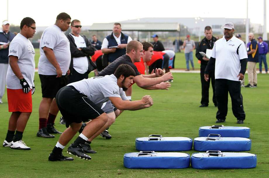 Participants work on a drill during 5th Annual Greater Houston Senior Football Showcase at the Houston Texans Methodist Training Center Saturday, Feb. 9, 2013, in Houston. The camp is for seniors who did not sign with a college to play football. College coaches were on hand to watch them run drills and offer scholarships. Photo: James Nielsen, Chronicle / © Houston Chronicle 2013