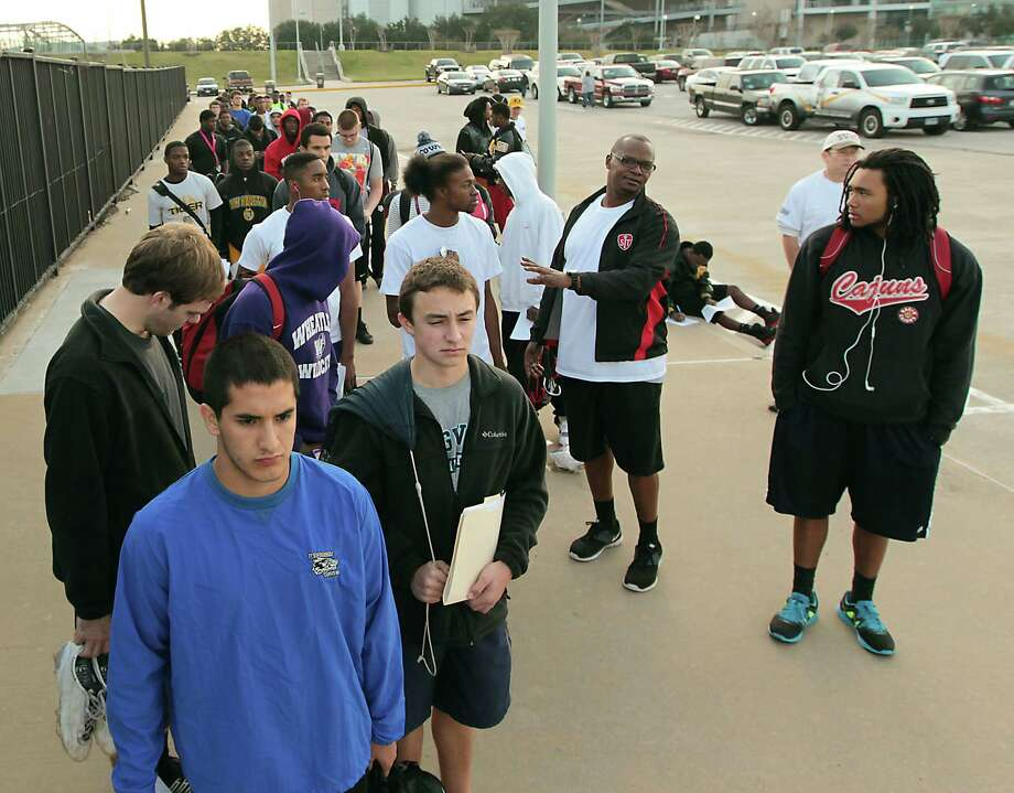Joseph Baez left, waits in line to register for the 5th Annual Greater Houston Senior Football Showcase at the Houston Texans Methodist Training Center Saturday, Feb. 9, 2013, in Houston. Photo: James Nielsen, Chronicle / © Houston Chronicle 2013