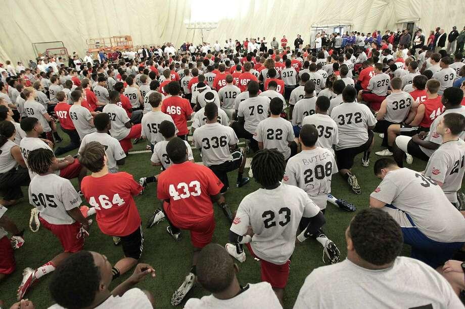 Participants of 5th Annual Greater Houston Senior Football Showcase listen to coaches at the Houston Texans Methodist Training Center Saturday, Feb. 9, 2013, in Houston. Photo: James Nielsen, Chronicle / © Houston Chronicle 2013