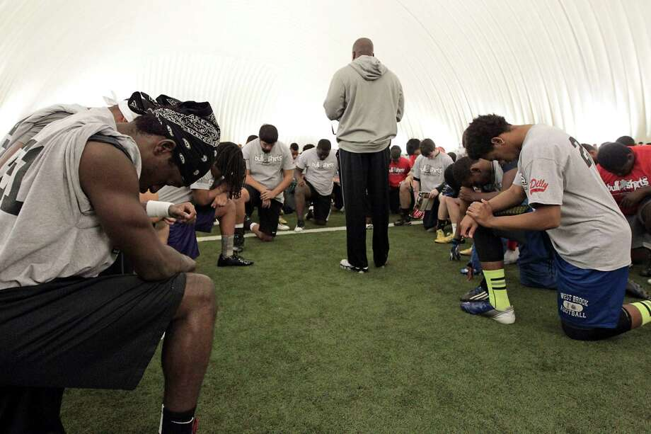 Former San Francisco 49ers player Tyrone Smith center, leads a prayer with participants of 5th Annual Greater Houston Senior Football Showcase at the Houston Texans Methodist Training Center Saturday, Feb. 9, 2013, in Houston. Photo: James Nielsen, Chronicle / © Houston Chronicle 2013