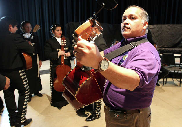 John Nieto, director of the Brackenridge High School Mariachi Band, tunes a guitarrón for a student before the start of their performance at The Texas High School Mariachi Competition by the Mexican American School Board Association at Edgewood ISD Theater of Performing Arts on Saturday, Feb. 9, 2013. Nieto has taught Mariachi music at Brackenridge for nearly 23 years. The group performed a song and two medleys for the competition. Photo: Kin Man Hui, San Antonio Express-News / © 2012 San Antonio Express-News