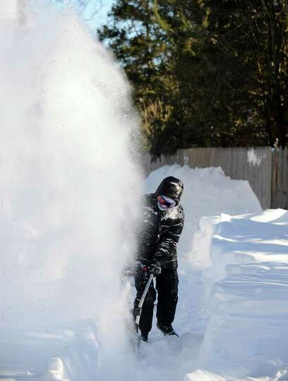 Kathleen Jackson clears her driveway on Stillson Rd. in Fairfield, Conn. on Friday, Feb. 9, 2013. So