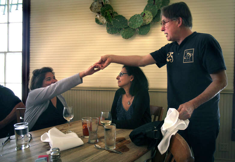 Owner of the Liberty Bar, Dwight Hobart, right, greets Grace Padron, left, and Patty Ortiz as the