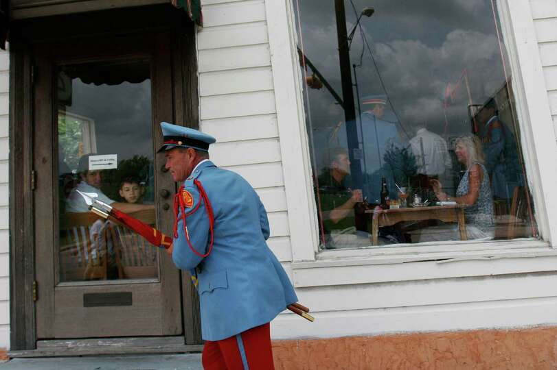 A member of the Cavaliers rushes past the Liberty Bar before the Battle of Flowers Parade, Friday