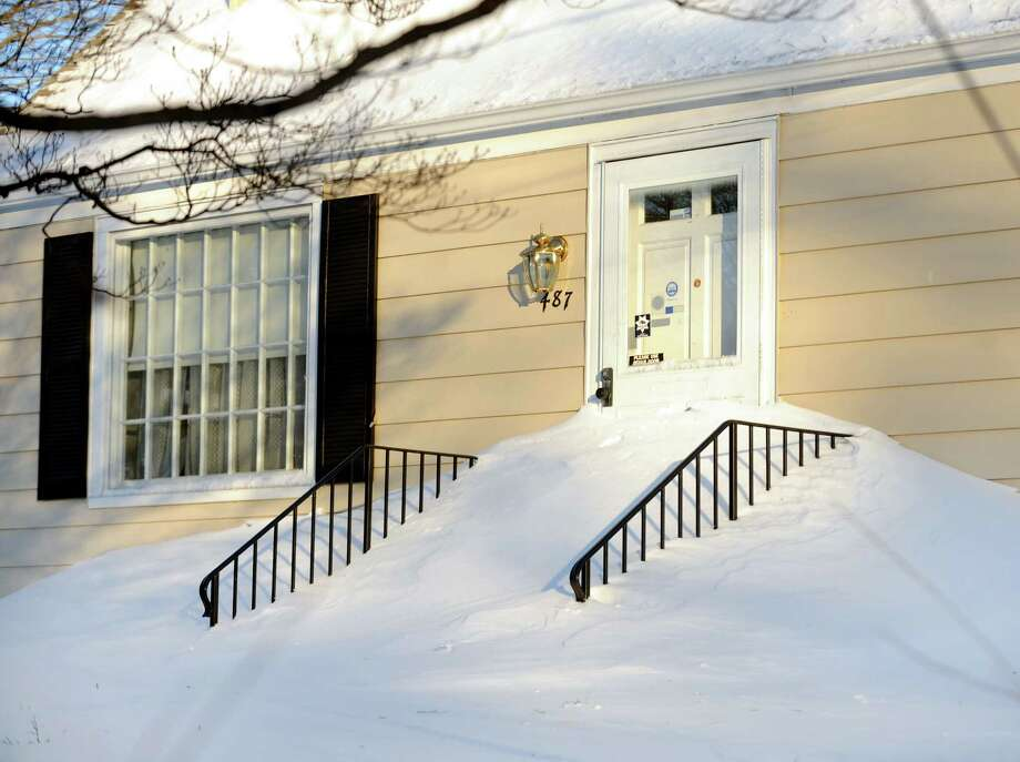 Snowdrifts went halfway up the door on this home Fairfield, Conn. on Friday, Feb. 9, 2013. Southwestern Connecticut was hit by one of the biggest snowstorms in history, a howling blizzard that dumped over two feet of snow across the area. Photo: Cathy Zuraw / Connecticut Post