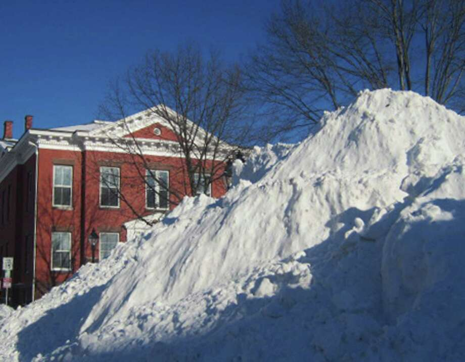 The plowed snow here might not really have been piled as high as the top of New Milford Town Hall Saturday afternoon, but it surely might have seemed so for those who ventured to the village center during the waning hours of the weekend storm. Feb. 9, 2013 Photo: Norm Cummings