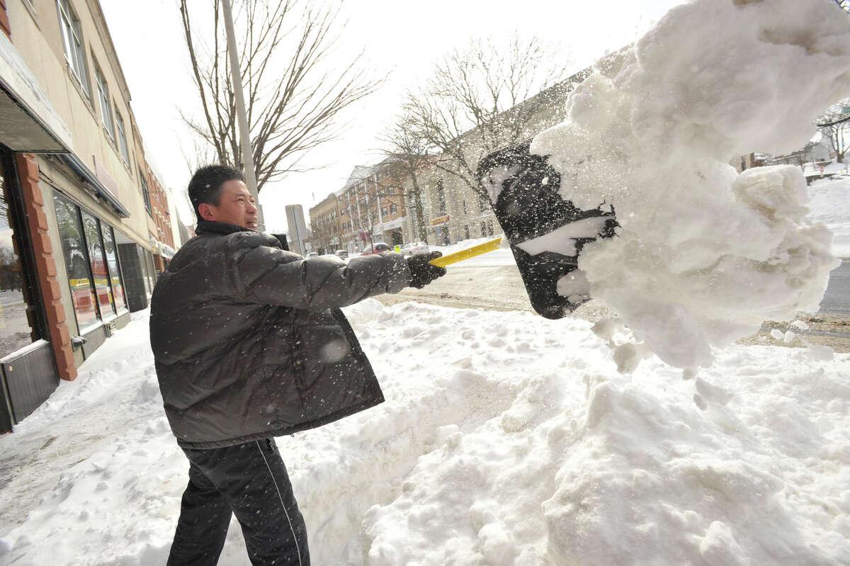 Shan Nee shovels out in front of his business on Main Street in Danbury on Saturday, Feb. 9, 2013.
