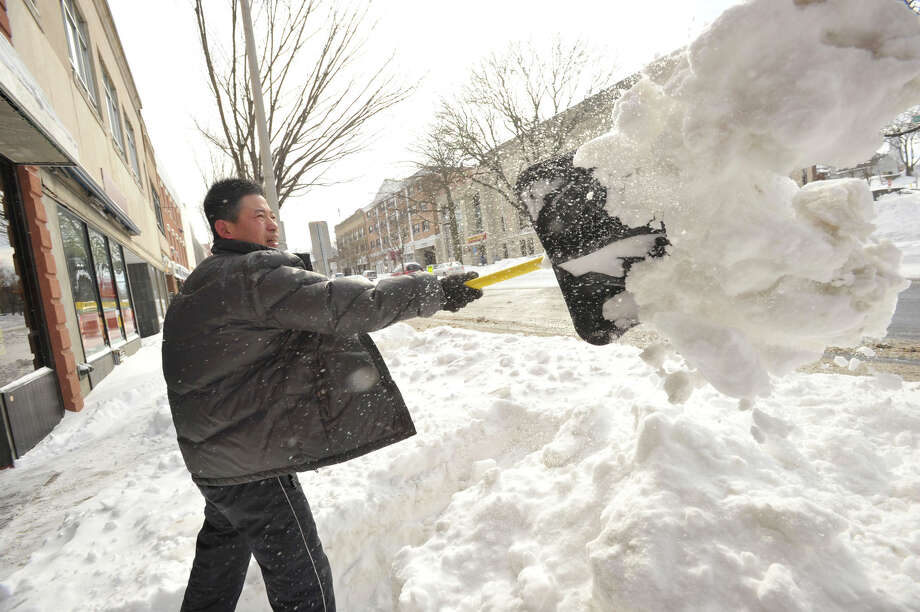 Shan Nee shovels out in front of his business on Main Street in Danbury on Saturday, Feb. 9, 2013. Photo: Jason Rearick/The News Times, Jason Rearick
