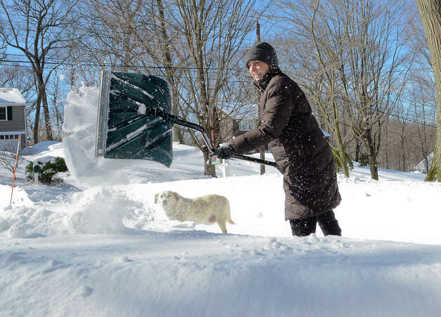 While her dog Hannah watches, Linda Moore contends with the snow in her driveway in Southport, CT on Sat., Feb. 9, 2013, following a blizzard that dumped up to three feet of snow across the state. Photo: Shelley Cryan / Shelley Cryan for the CT Post/ freelance Shelley Cryan