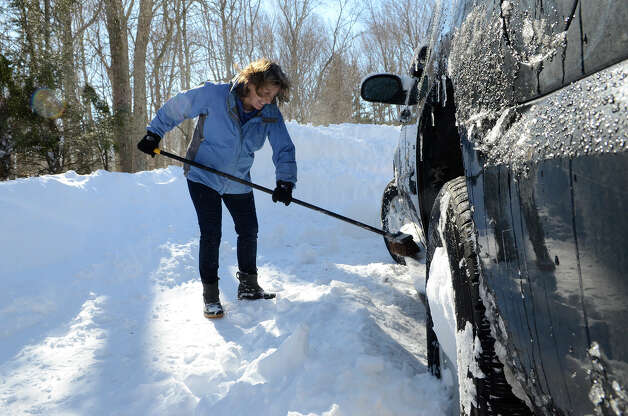Julie Wyckoff clears snow from her car in Southport, CT on Sat., Feb. 9, 2013, following a blizzard that dumped up to three feet of snow across the state. Photo: Shelley Cryan / Shelley Cryan for the CT Post/ freelance Shelley Cryan