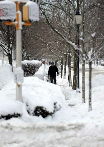 A pedestrian walks down a snowy sidwalk in Stamford, Conn., on Saturday, February 9, 2013. Photo: Lindsay Perry / Stamford Advocate