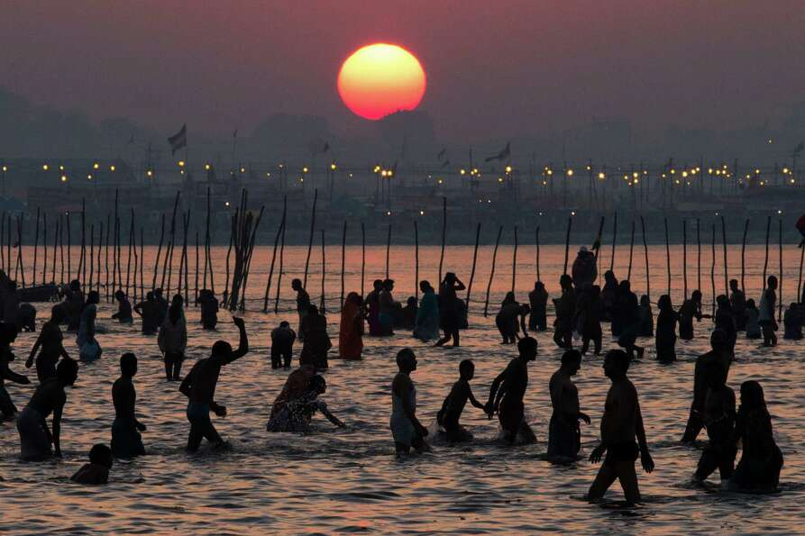 Hindu devotees bathe on the banks of Sangam, the confluence of the holy rivers Ganges, Yamuna and th