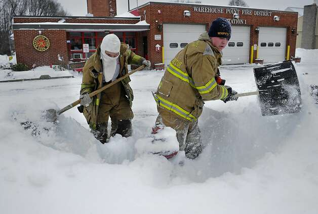 Junior firefighter Adam Krach, left, and firefighter Steve Ellis of the Warehouse Point Fire Department dig snow from a hydrant outside their station in East Windsor, Conn. on Saturday, Feb. 9, 2013. A behemoth storm packing hurricane-force wind gusts and blizzard conditions swept through the Northeast overnight.  Photo: Jessica Hill, Associated Press