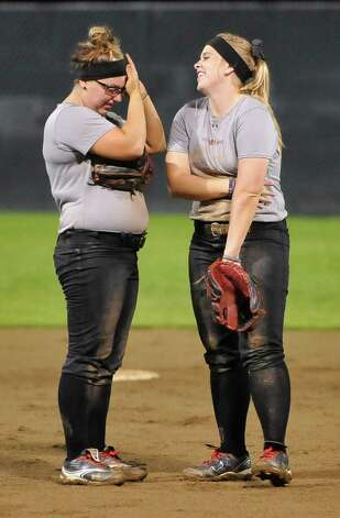Lauren Gambone, left, talks with Alyssa Burnett, right, in the infield. Lamar softball is having it's first season since 1987. Thursday night found the girls team getting practice done at the Ford Park complex. They will open their 2013 season on Saturday.   Dave Ryan/The Enterprise Photo: Dave Ryan