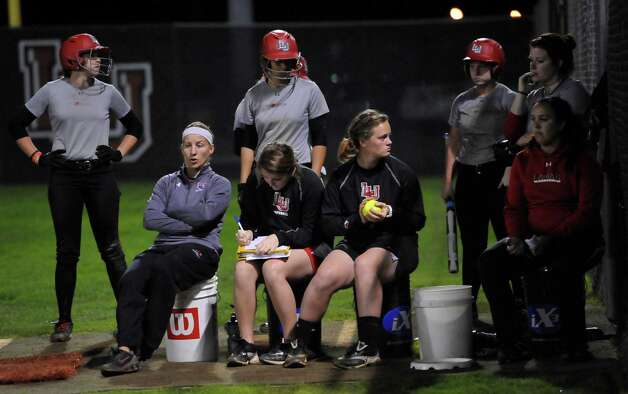 Head coach Holly Bruder, bottom left, and her coaching staff take up their seats to watch practice. Lamar softball is having it's first season since 1987. Thursday night found the girls team getting practice done at the Ford Park complex. They will open their 2013 season on Saturday.   Dave Ryan/The Enterprise