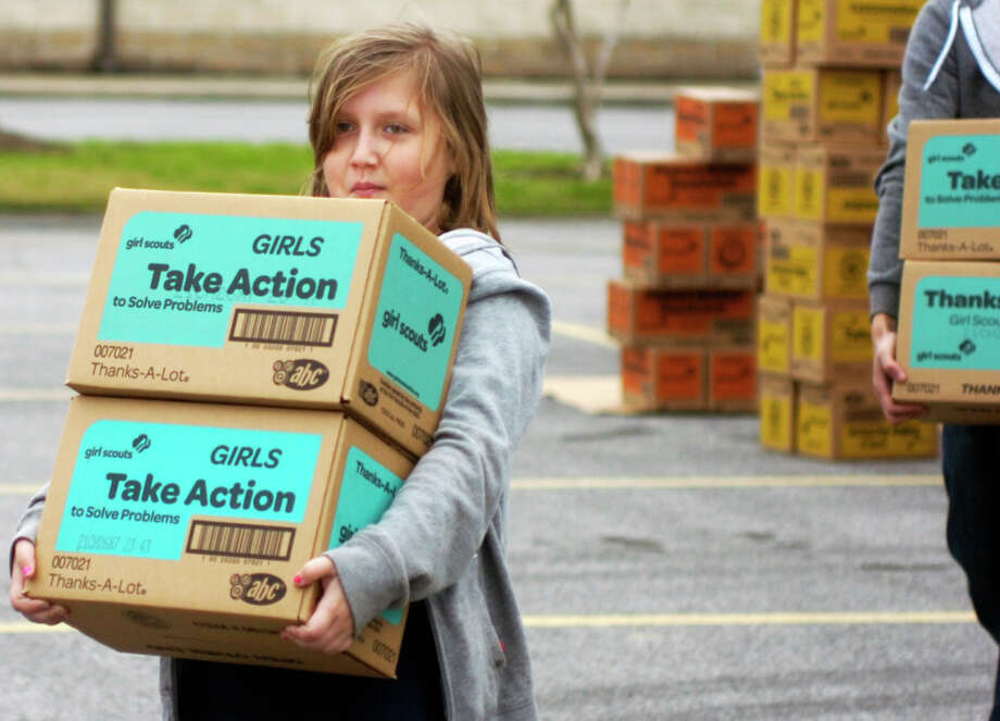 Junior Girl Scout Mackenzie Graham carries boxes of cookies to a waiting vehicle Saturday at Wesley United Methodist Church. A shipment of 60,000 boxes of cookies arrived there for the annual Girl Scout cookie sale. Photo: Sarah Moore