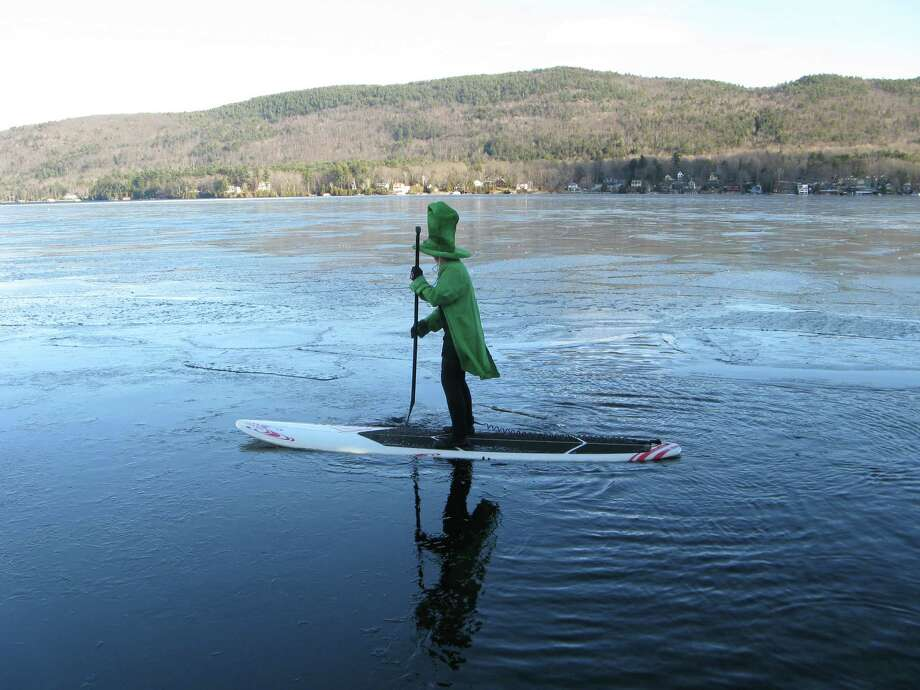 "Is that a leprechaun on Lake George? Well, close. It?s Colleen O'Shea paddle boarding during the Lake George Winter Carnival last season (and looking forward to St. Patrick?s Day). ""I received the paddle board for Christmas and could not wait until summer to try it out, so I decided to have some fun and dress like a leprechaun and paddle board in the freezing weather in hopes that I would not fall into the icy Lake George water! It was a cold windy day that took some balance and skill to not fall off the board! I certainly put a smile on the face of many adults and children that afternoon,"" she says.  (Colleen O'Shea)"