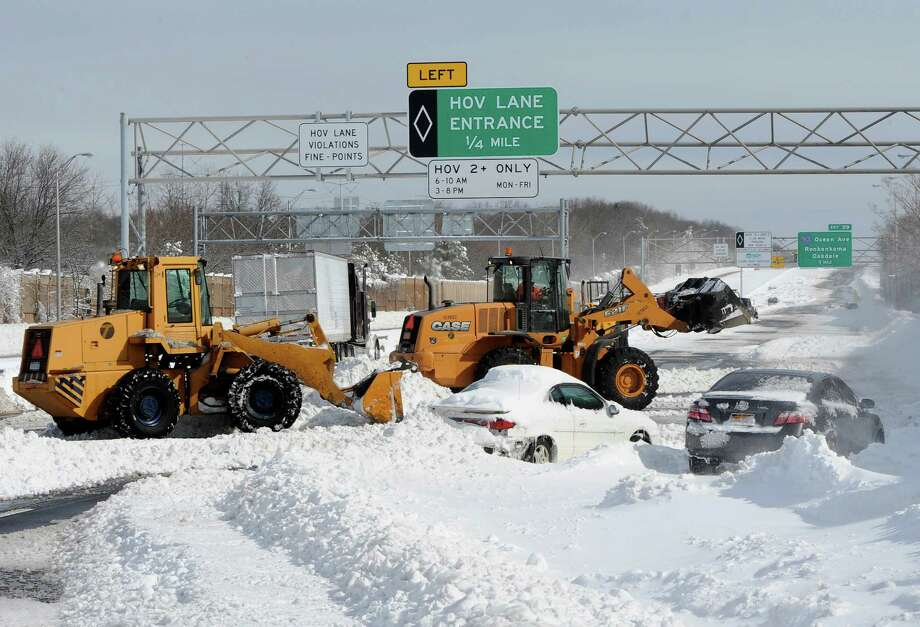 Payloaders clear snow from the Long Island Expressway just west of exit 59 Ocean Ave where several cars and a truck are abandoned after a snow storm on Saturday, Feb. 9, 31, 2013, in Ronkonkoma , N.Y. (AP Photo/Kathy Kmonicek) Photo: Kathy Kmonicek