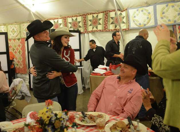 Army wounded warrior Doug  McIntosh, left, embraces Miss Rodeo Nebraska Samantha Chycka during the KCI Rodeo Star Experience dinner for military personnel  during the third day of Stock Show & Rodeo on Saturday, Feb. 9, 2013. Photo: Billy Calzada, San Antonio Express-News / San Antonio Express-News
