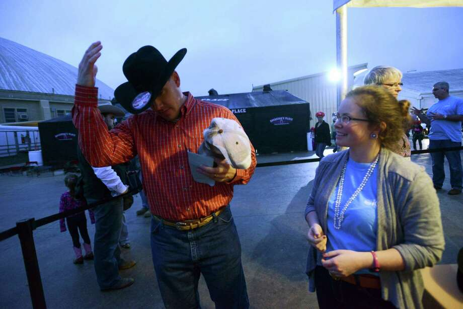 Chad Bartosh tries dons a hat given to him during the KCI Rodeo Experience dinner for wounded warriors during the third day of Stock Show & Rodeo on Saturday, Feb. 9, 2013. Mallory Boyle watches. Photo: Billy Calzada, San Antonio Express-News / San Antonio Express-News