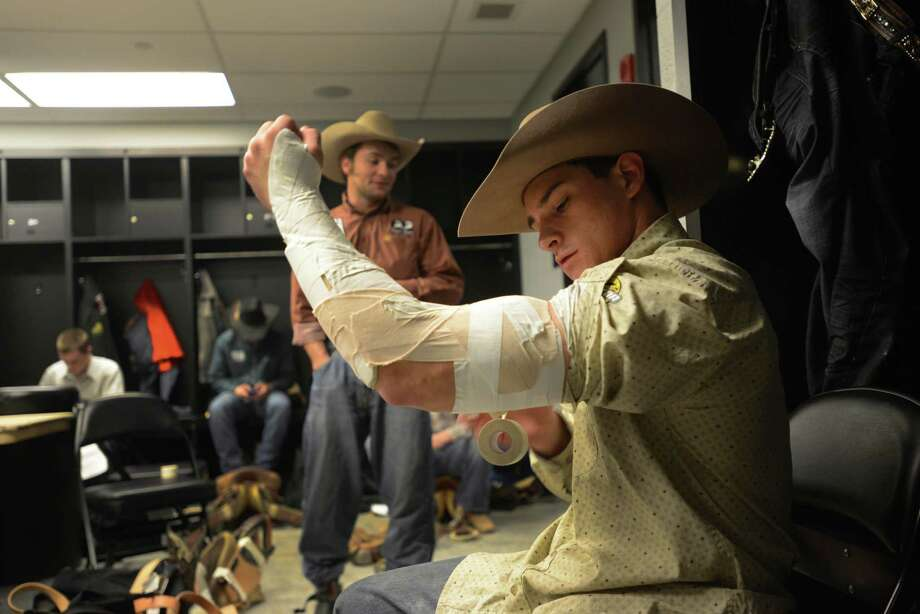 Bareback bronc rider Ty Fast Taypotat tapes his arm in preparation for his ride during the third day of Stock Show & Rodeo on Saturday, Feb. 9, 2013. Photo: Billy Calzada, San Antonio Express-News / San Antonio Express-News