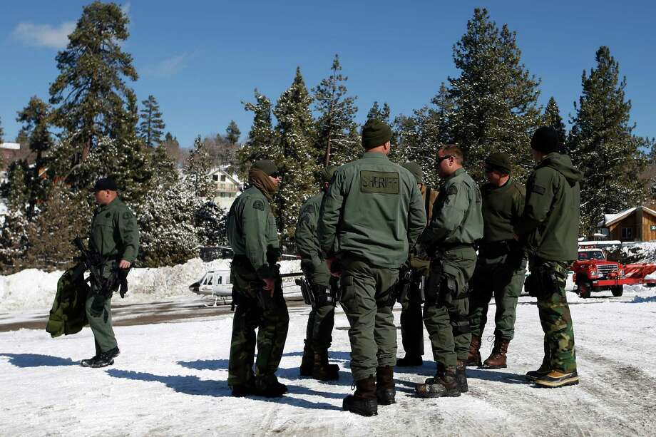 San Bernardino County Sheriff's deputies gather at the command post in Big Bear Lake, Calif, Saturday, Feb. 9, 2013.  Clear skies allowed aircraft with heat-sensing technology to aid scores of officers searching in the snow-covered San Bernardino Mountains for Christopher Dorner, the former Los Angeles police officer suspected of killing three people in a vengeance-fueled rampage aimed at those he blames for ending his career. (AP Photo/Jae C. Hong) Photo: Jae C. Hong