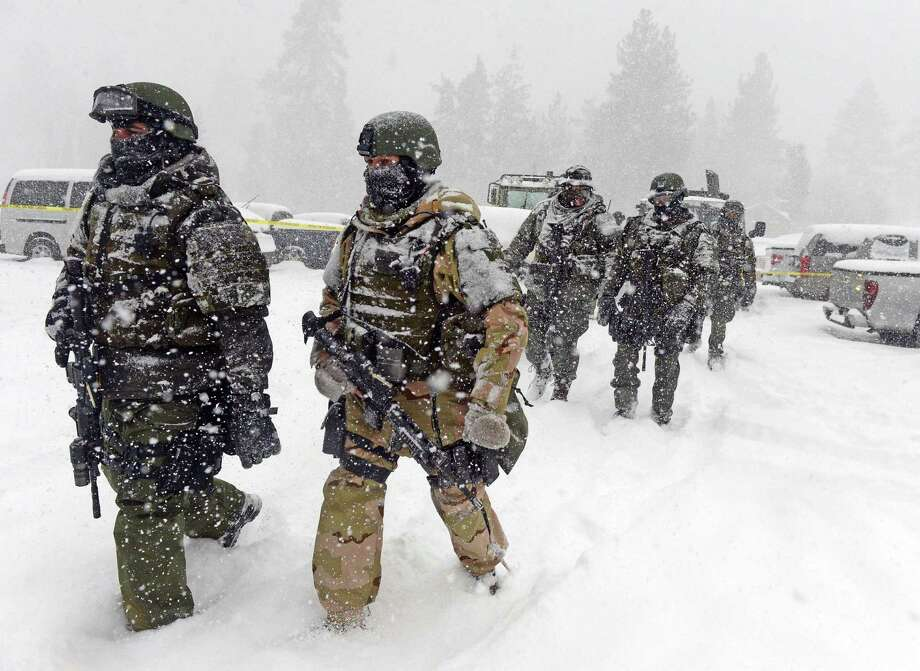 A San Bernardino County Sheriff SWAT team returns to the command post at Bear Mountain near Big Bear Lake, Calif. after searching for Christopher Jordan Dorner on Friday, Feb. 8, 2013. Search conditions have been hampered by a heavy winter storm in the area. Dorner, a former Los Angeles police officer, is accused of carrying out a killing spree because he felt he was unfairly fired from his job. (AP Photo/The Inland Valley Daily Bulletin, Will Lester, Pool) Photo: Will Lester