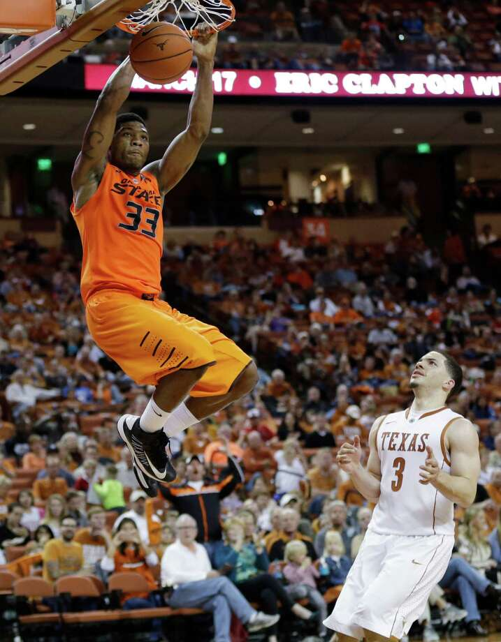 Oklahoma State's Marcus Smart (33) puts the finishing touch on two of his 23 points as Texas' Javan Felix (3) does little more than watch in the second half. Photo: Eric Gay, STF / AP