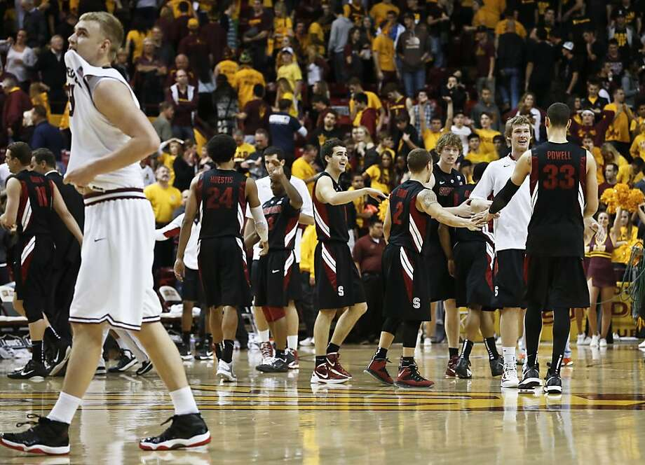 Arizona State's Jonathan Gilling (left) walks off the court as Stanford's Dwight Powell (33) celebrates a victory with teammates. Photo: Ross D. Franklin, Associated Press