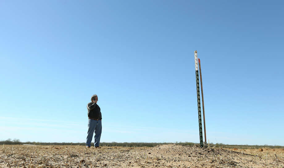 Harvey Howell, president of H.H. Howell, Inc., an oil and gas exploration company in San Antonio, calls to check the status of the arrival of a drilling rig at a site in Frio County, Thursday, Jan. 17, 2013. The third generation wildcatter, Howell, was investing $1.3 million in the drilling operation, marked by the stake in the foreground. He calculated his odds at finding oil at 10-1against. Photo: Jerry Lara, San Antonio Express-News / © 2013 San Antonio Express-News