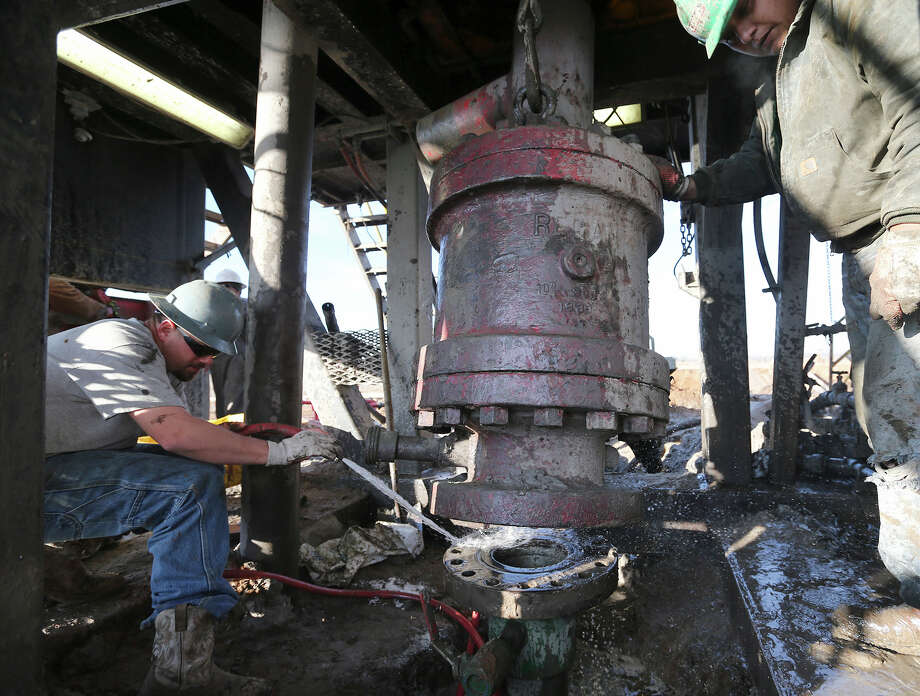 Toolpusher Chris Graham, 28, left, and floorhand Miguel Ortiz, help install blowout prevention equipment at a drilling site in Frio County, Saturday, Jan. 19, 2013. Photo: Jerry Lara, San Antonio Express-News / © 2013 San Antonio Express-News