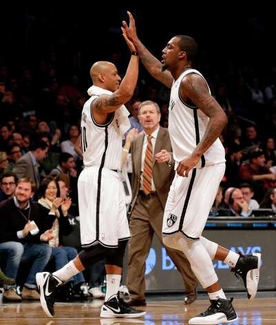 Brooklyn nets interim head coach P.J. Carlesimo watches as Keith Bogans (left) celebrates with center Andray Blatche at the Barclays Center, Friday, Feb. 1, 2013 in New York. The Nets defeated the Bulls 93-89. Photo: Kathy Willens, Associated Press / AP