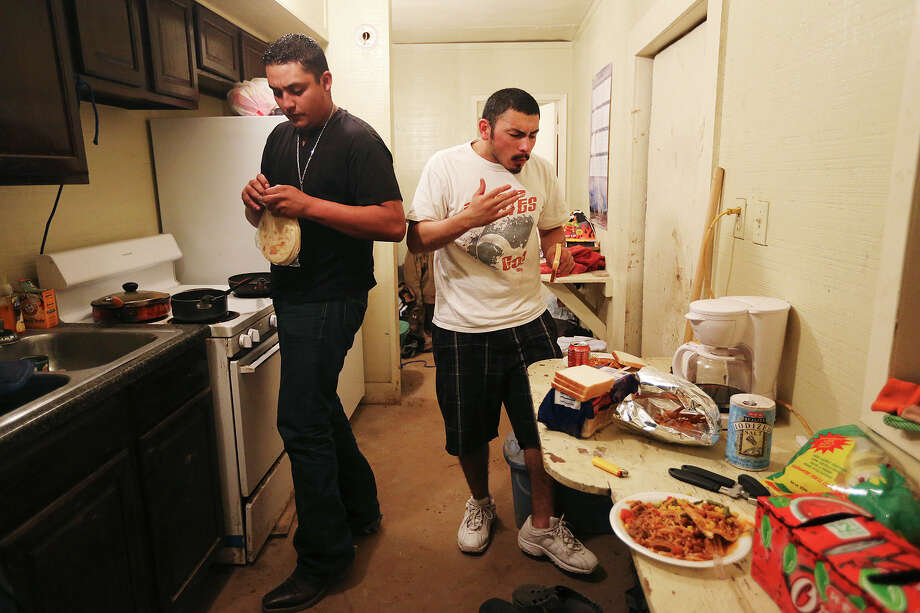 Floorhand Miguel Ortiz, 21, of Alamo, opens a package of homemade tortillas made by his mother, as he and fellow floorhand, J.B. Espinoza, 21, of Freer, eat dinner inside the company provided housing at a drilling site in Frio County, Sunday, Jan. 20, 2013. Photo: Jerry Lara, San Antonio Express-News / © 2013 San Antonio Express-News