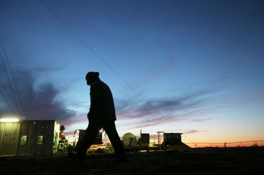 Floorhand Juan Mata, 32, of Alice, Texas walks back to the rig after talking with the toolpusher at the start of the overnight shift at a drilling site in Frio County, Sunday, Jan. 20, 2013. Photo: Jerry Lara, San Antonio Express-News / © 2013 San Antonio Express-News