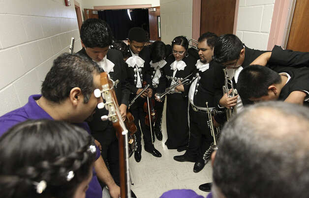 The Brackenridge musicians pray before taking the stage at the competition, which featured 16 mariachi bands from across the state. Photo: Photos By Kin Man Hui / San Antonio Express-News