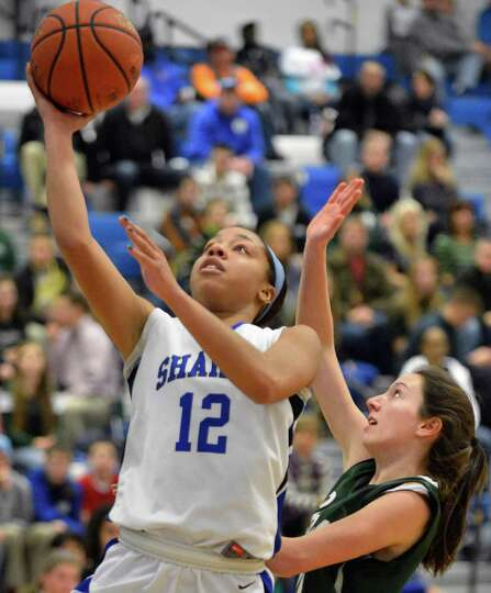Shaker's #12 Madison Rowland, left, scores against Shen defender #42 Erin Hulbert during Saturday's