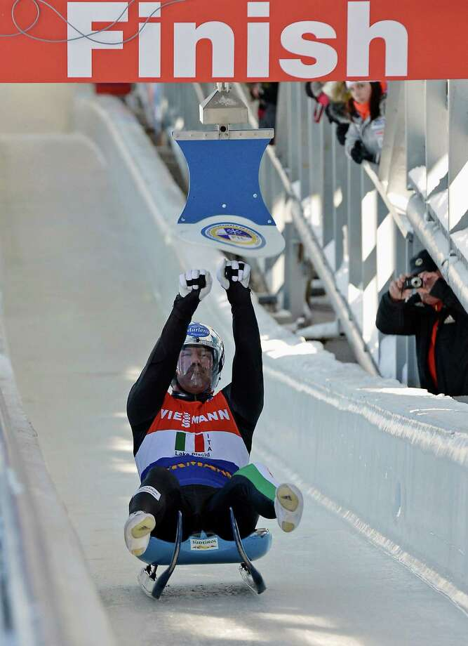 Armin Zoeggeler, of Italy, hits the target during the team relay competition at the luge World Cup event in Lake Placid, N.Y., Saturday, Feb. 9, 2013. Italy finished third in the event. (AP Photo/John DiGiacomo) Photo: John DiGiacomo
