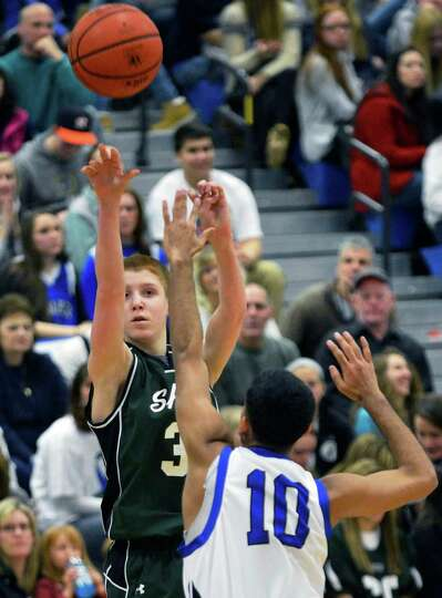Shen's #3 Todge Campbell tries a three pointer against Shaker's #10 Dylan Molloy during Saturday's g