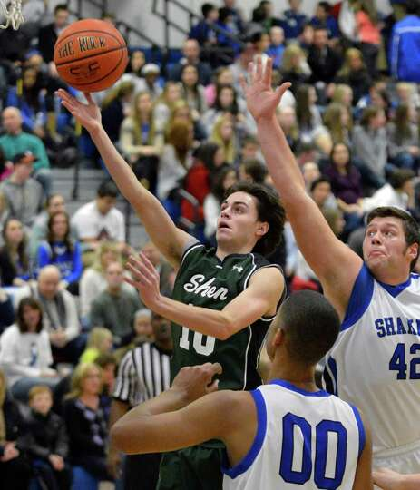 Shen's #10 Malik Dare gets around Shaker's #42 David Morrison, at right, on his way to the basket du