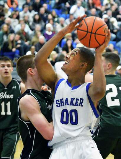 Shaker's #00 Malik Dare battles Shen defenders during Saturday's game at Shaker High in Colonie Feb.