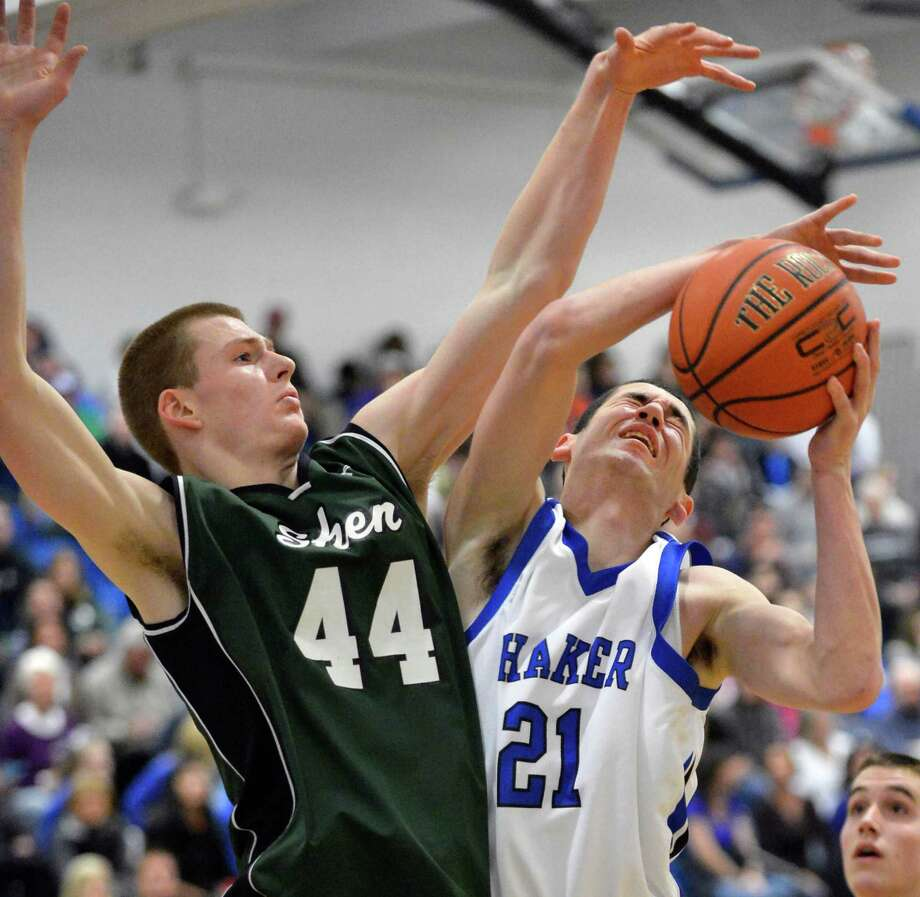 Shaker's #21 Chris Landers gets fouled as he drives to the basket covered by Shen's #44 Brandon Fischer, at left, during Saturday's game at Shaker High in Colonie Feb. 9, 2013.  (John Carl D'Annibale / Times Union) Photo: John Carl D'Annibale / 10021092A