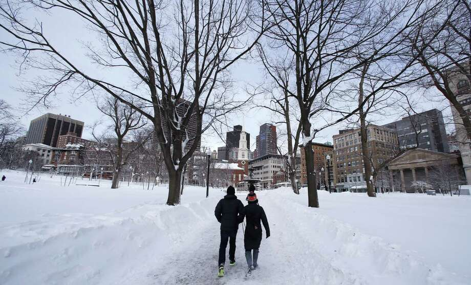 A couple walks through Boston Common in Boston, Saturday, Feb. 9, 2013.  The Boston area received about two feet of snow from a winter storm. A howling storm across the Northeast left the New York-to-Boston corridor shrouded in 1 to 3 feet of snow Saturday, stranding motorists on highways overnight and piling up drifts so high that some homeowners couldn't get their doors open. More than 650,000 homes and businesses were left without electricity. (AP Photo/Charles Krupa) Photo: Charles Krupa, Associated Press